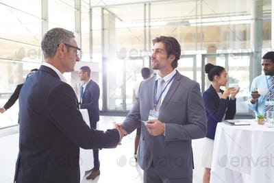 Business people shaking hand during a seminar. Diverse business people are interacting behind them