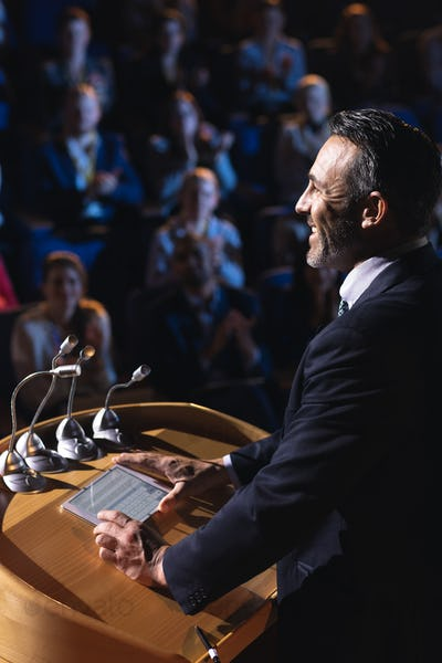 Side view of Caucasian businessman standing and giving presentation in the auditorium