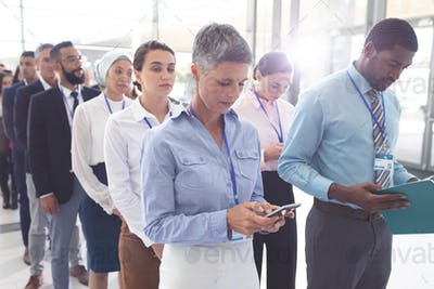 Diverse business people standing in queue in lobby at office and looking their mobile phone