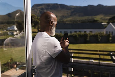 Rear view of a handsome senior African American man using mobile phone on the balcony at home