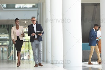 Businesswoman and businessman interacting with each other while walking in lobby office