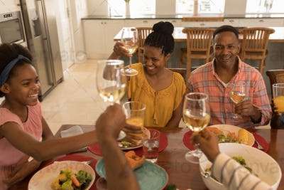 Multi-generation family toasting glasses of white wine on dining table at home
