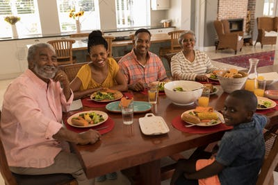 Multi-generation family sitting at the dining table for having meal at home