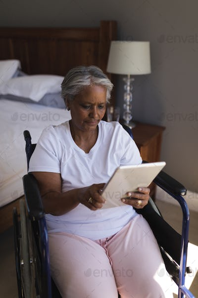 Front view of a disabled senior African American woman using digital tablet in bedroom at home