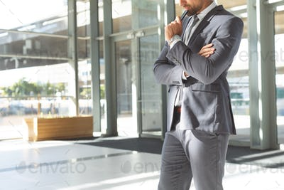 Thoughtful young Caucasian businessman with head down on his mobile phone standing in office
