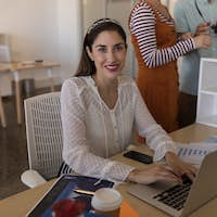 Portrait of beautiful Caucasian female executive smiling while using laptop at desk in modern office