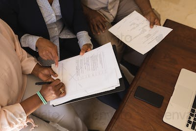 Senior woman signing property contract with real estate agent and senior man while sitting on a sofa
