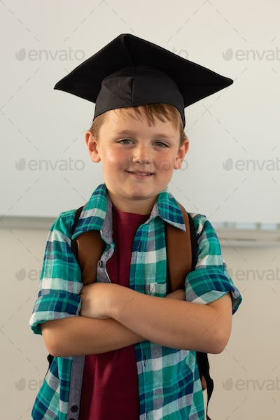 Front view of happy Caucasian boy in graduation cap standing in a classroom at elementary school