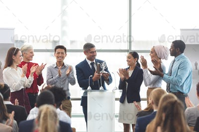 Businessman holding award on podium with colleagues at business seminar