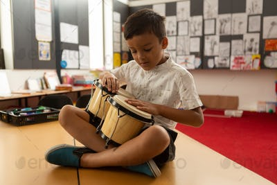Schoolboy sitting on desk and playing bongo in a classroom at elementary school