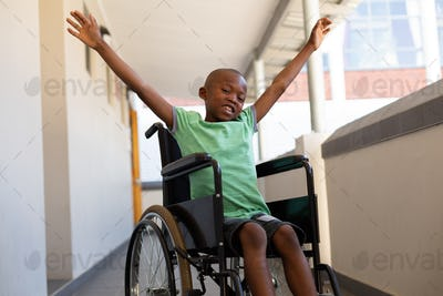 Schoolboy with arms stretched out sitting in a wheelchair in a corridor at elementary school