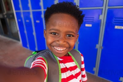 Front view of a happy African American schoolboy standing in the corridor at school