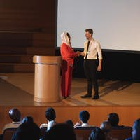 Business colleague standing with each other in front of the audience in auditorium