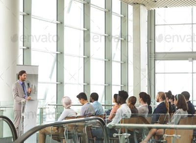 Businessman speaking in front of diverse group of business people sitting at business seminar