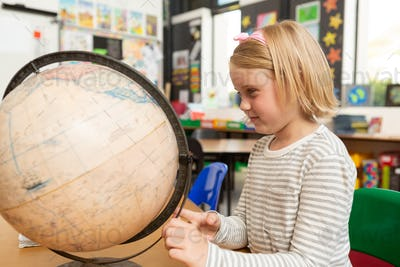 Side view of a Caucasian schoolgirl studying a earth globe at desk in a classroom at school
