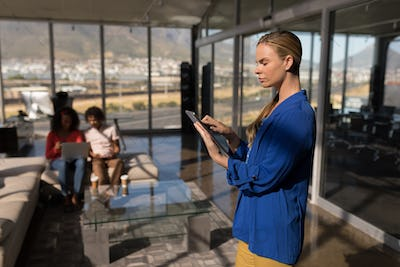 Female executive using digital tablet in modern office