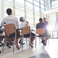 Diverse young business people listening while sitting on wooden chairs in conference room