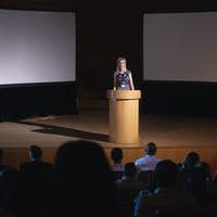 Businesswoman standing around podium and giving presentation to the audience in auditorium