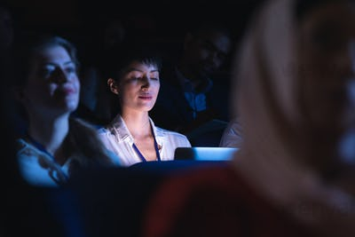 Businesswoman holding and looking at laptop while sitting in the auditorium
