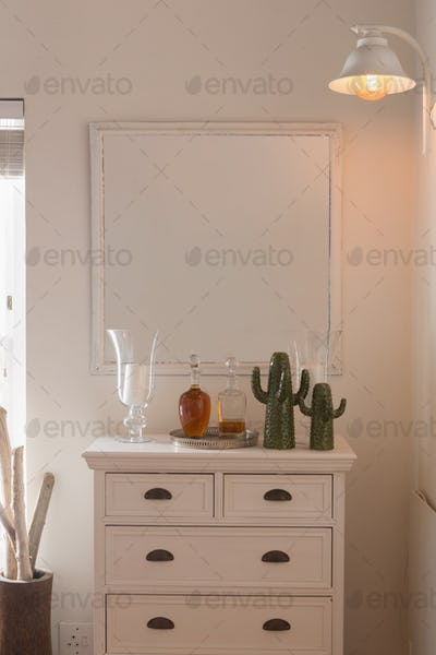 Modern mirror fixed above a cabinet supporting a vases and false cactus at home