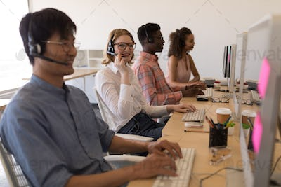 Diverse young executives working on personal computer while talking on headset in modern office.