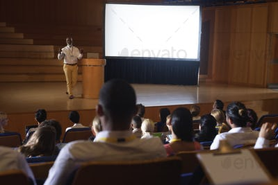 High view of matured African-American businessman standing and giving presentation in auditorium