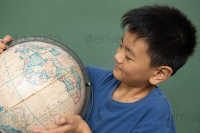Schoolboy looking at a globe in a classroom at elementary schoo