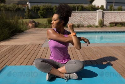 young woman performing stretching exercise next to the swimming pool in the backyard