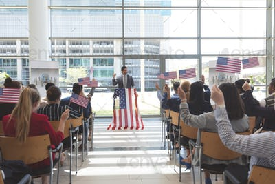 Front view of american businessman speaks in a business seminar in office building