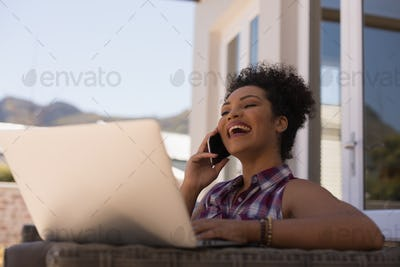 Beautiful woman talking on mobile phone while using laptop on the terrace at home