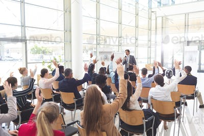 Diverse business people listening and raising hands in conference