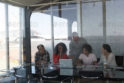 Front view of multi-ethnic business colleagues discussing plans over laptop in modern office