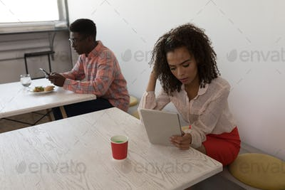 male and female executives using electronic devices in canteen at office