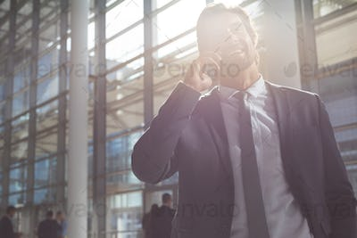 Low angle view of happy young businessman talking on mobile phone in lobby office