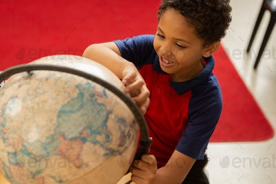 playful schoolboy studying globe at desk in a classroom at elementary school