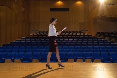 Businesswoman practicing and learning script while walking in the auditorium
