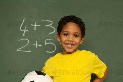 Schoolboy with football looking at camera against greenboard in a classroom at elementary school