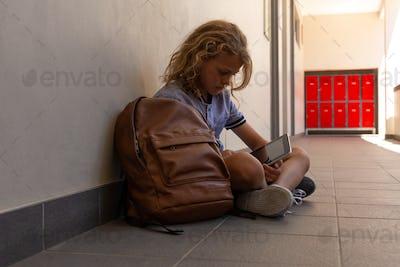 Schoolgirl sitting on the floor with her school bag and using digital tablet in school corridor