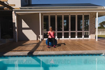 Middle-aged woman exercising with dumbbells and exercise ball in the backyard of home