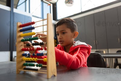 Cute schoolboy learning math with abacus at desk
