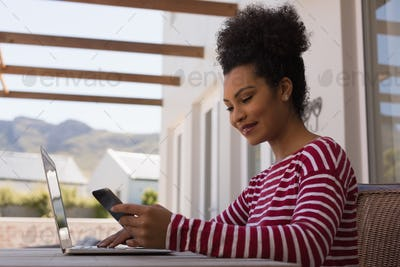 Young woman using her mobile phone while working on laptop at home