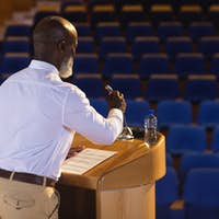 Side view of matured African-American businessman practicing for speech in the empty auditorium