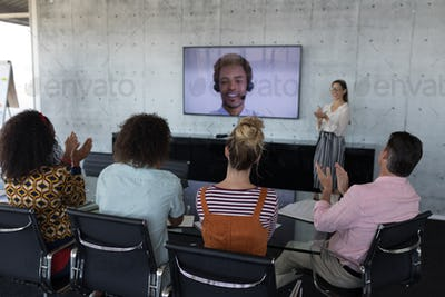 Young business colleagues applauding while attending a video call in a conference room