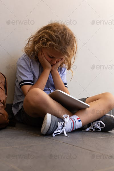 Schoolgirl sitting on the floor with head on hands in corridor and holding a digital tablet