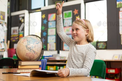 Side view of a Caucasian schoolgirl raising her hand at desk in the classroom at school