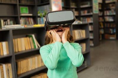 Surprised schoolgirl using virtual reality headset in library