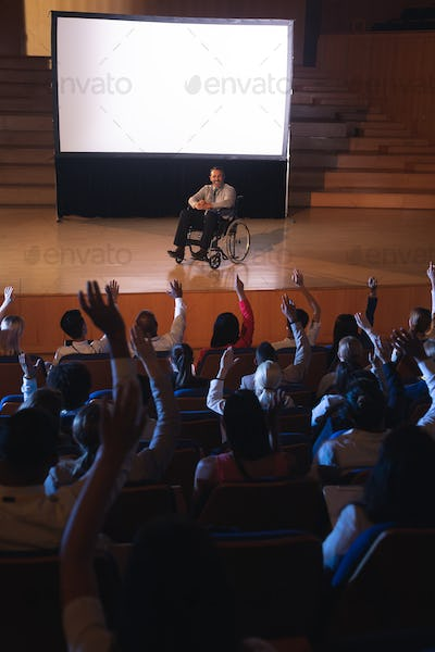Businessman sitting on a wheelchair and giving presentation while audience raising hand