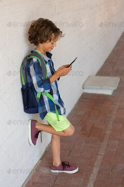Schoolboy using his mobile phone while leaning against a wall in the corridor