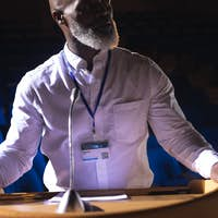 Old businessman looking and thinking while standing on stage in auditorium
