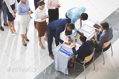 Business people checking in at conference registration table in office lobby